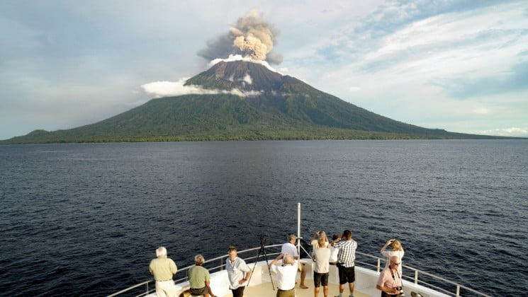 people stand at the bow of the small ship cruise to look at the manum island volcano in the distance in the pacific islands