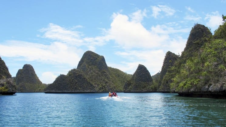 a boat motors toward green mountains towering above the water in papua new guinea in the pacific islands