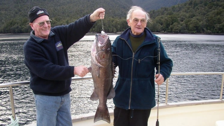 two men hold a large fish caught on a fishing excursion while sailing on the affinity small ship through new zealand's fiordland