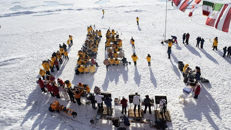 passengers from the north pole expedition sit at tables on the snow for a barbecue