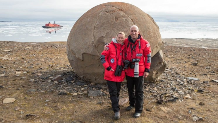 a couple poses in front of a giant round rock on a beach in the arctic, near the north pole