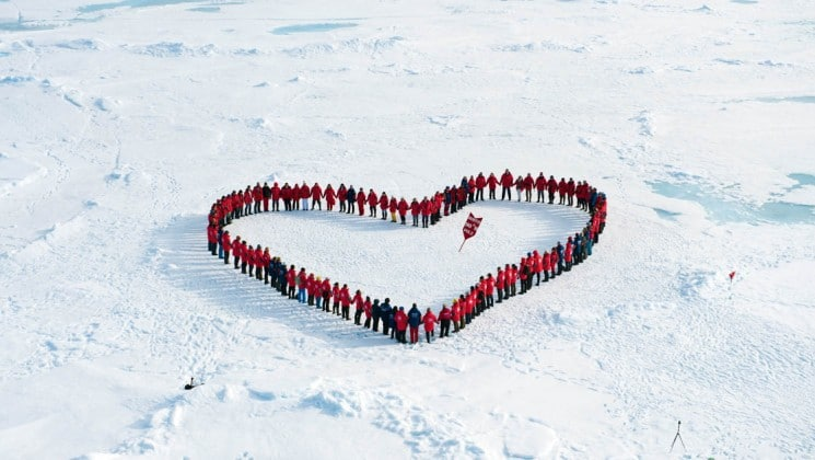passengers on the top of the world expedition form a heart shape around the north pole
