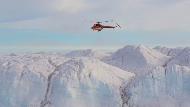 a helicopter flies above a glacier on its way to the north pole