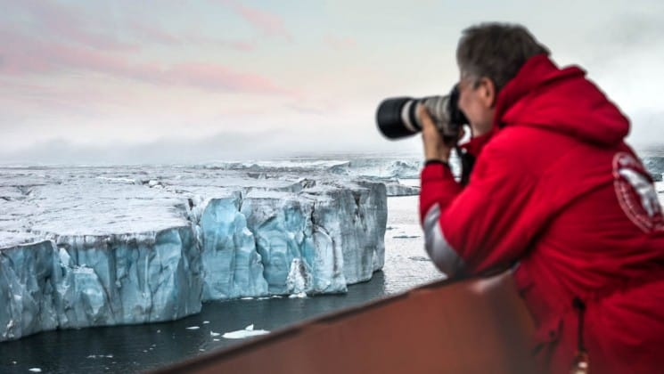 a passenger leans over the railing on board fifty years of victory ship to take a photograph of an iceberg at sunset in the north pole