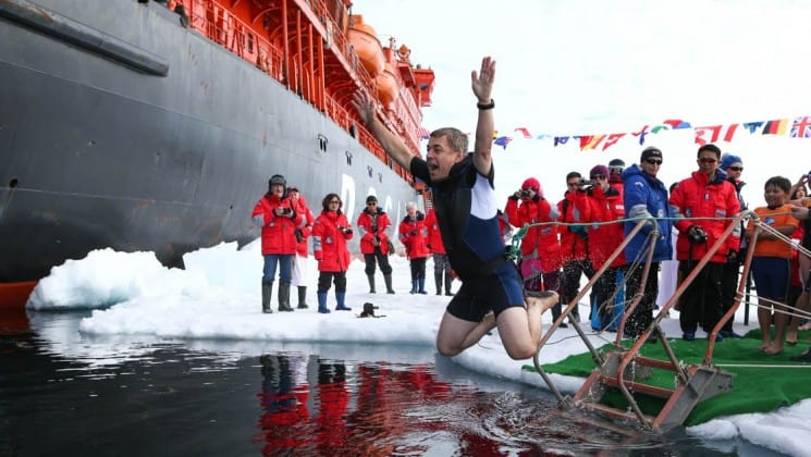 a man jumps into the ocean to take the polar plunge, with the fifty years of victory ship and other passengers in the background in the north pole
