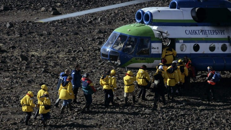 passengers on the expedition to the north pole board a helicopter in the arctic circle