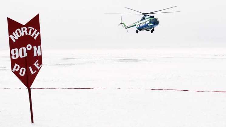 a helicopter lands on a snow field behind a sign that marks the north pole at 90 degrees north