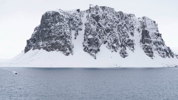 a rocky island covered in snow rises up from a grey ocean in the northwest passage of canada's arctic