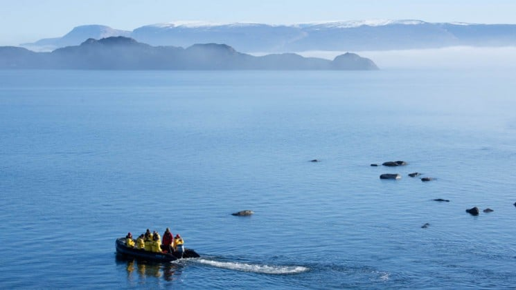 a zodiac boat motors into the open seas of the arctic circle with mountains in the distance