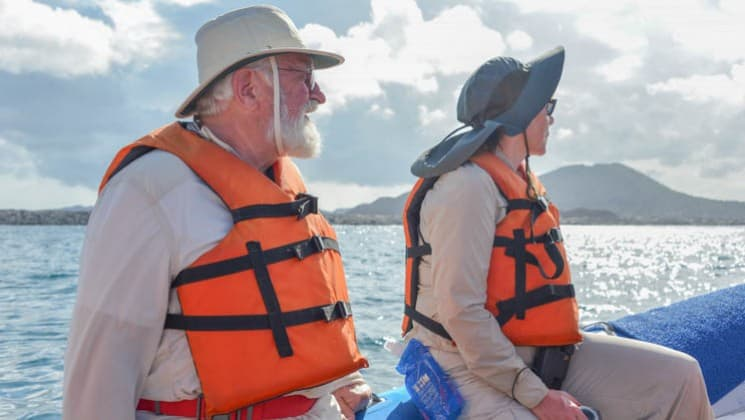 two guests from the ocean spray cruise ship wearing orange life jackets sit on a zodiac boat while motoring over the ocean to the galapagos islands