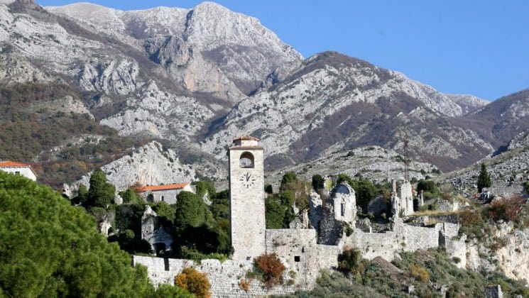 An old town in montenegro, nestled between trees and cliffs