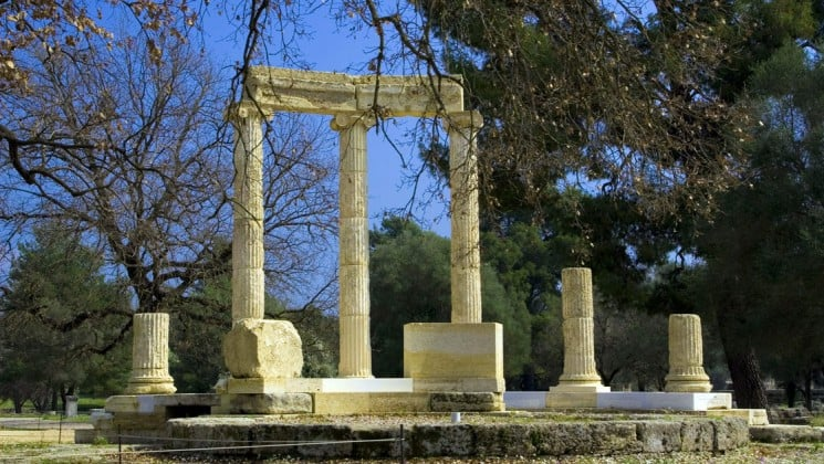 ancient greek columns standing in olympia with trees in the foreground