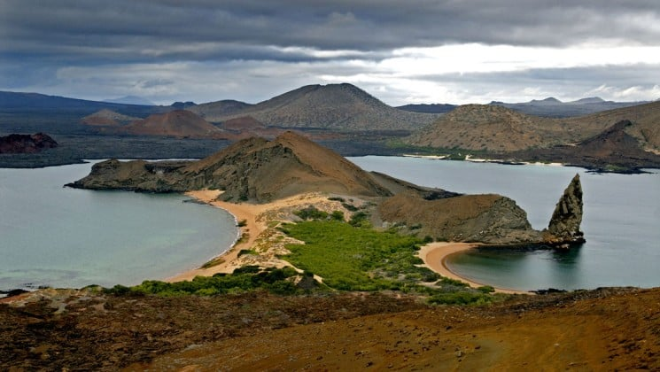 An aerial view of the Galapagos Islands, with grassy slopes and open beaches and a pinnacle rock jutting out of the water, where the Origin and Theory cruise ships go