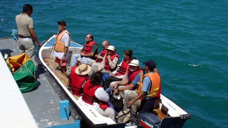 Passengers in life jackets board a small boat to travel back to the Grace yacht, after a day of visiting wildlife and exploring the Galapagos islands