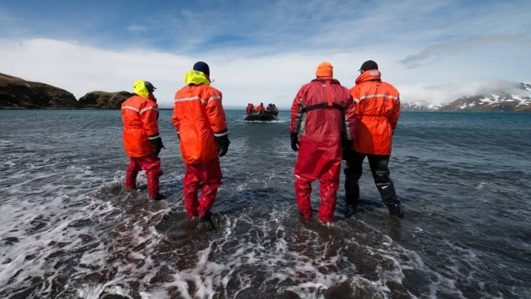 Four people on the expedition team launch a zodiac into the ocean in antarctica