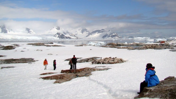 Guests on the Polar Circle Air Cruise take in the view from land of antarctica's snowy vistas and mountains