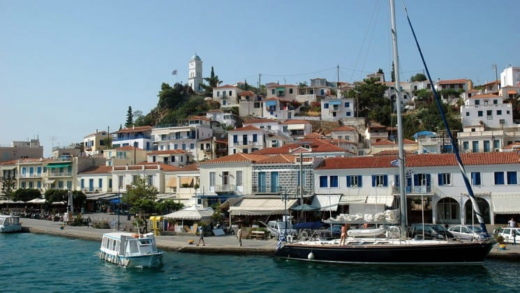 looking up at a town with red-tiled roofs and a sidewalk along the water in poros, a greek island in the aegean sea