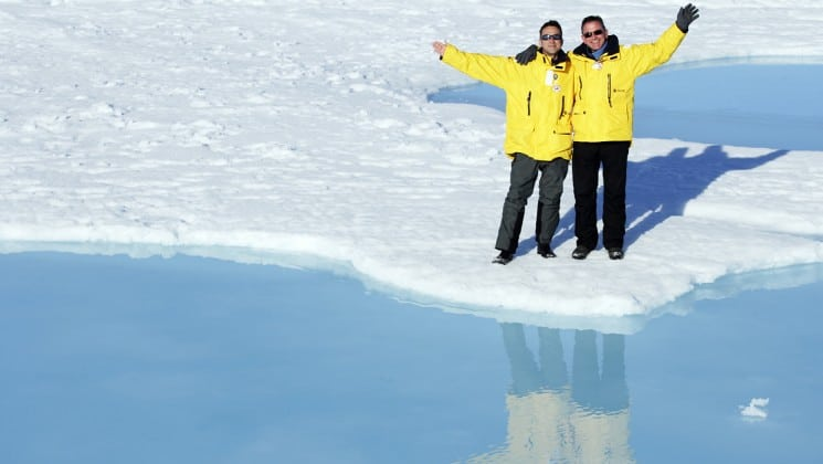 two people in yellow parkas pose for a photo on the icepack in the north pole