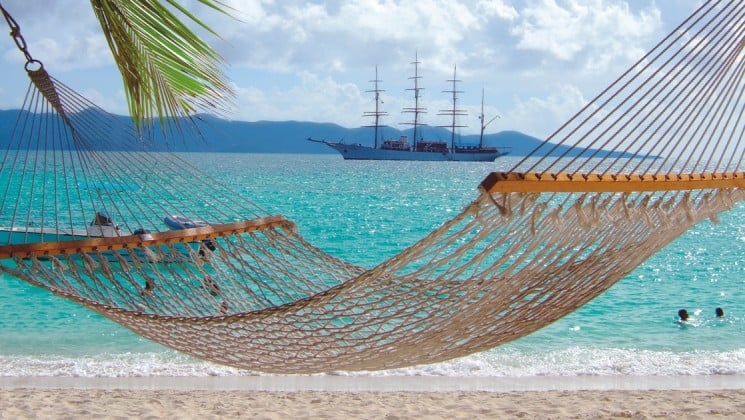 an empty hammock hangs on a white sand beach with the tropical caribbean ocean and the sea cloud small ship sailing in the background