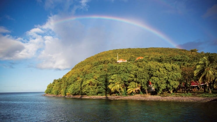 a rainbow crests above a lush, tropical island on the caribbean sea near barbados