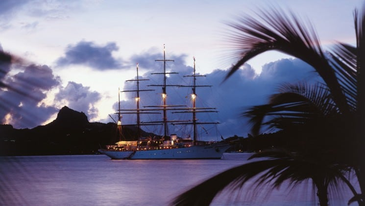 lights illuminate the masts of the small ship sea cloud at sunset on the tropical caribbean ocean with palm trees silhouetted in the foreground