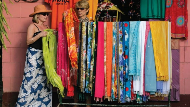 colorful and mixed print sarongs hang while a guest from the small ship sea cloud goes shopping in the caribbean