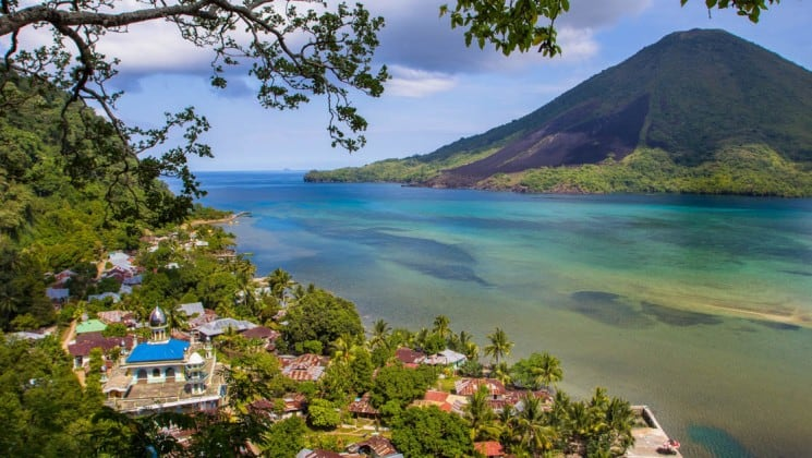 A tropical view of the ocean and red-tiled houses nestled on the trees in the Banda Islands, Indonesia