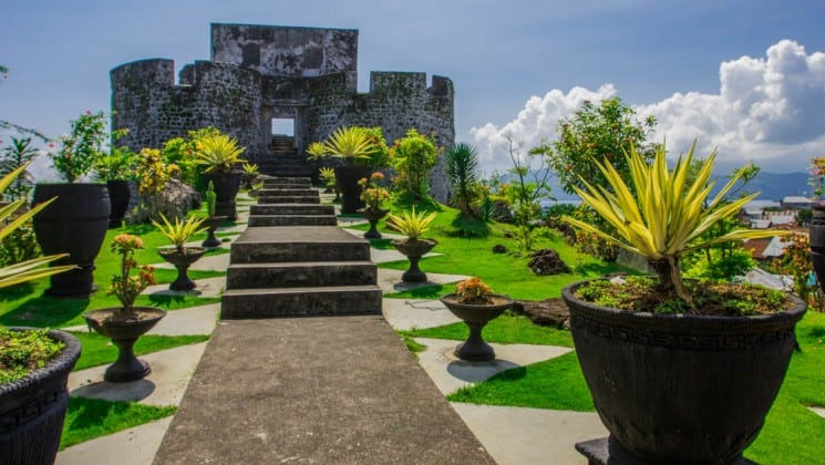 A pathway up stone steps lined by a garden to a dutch fort in ternate indonesia