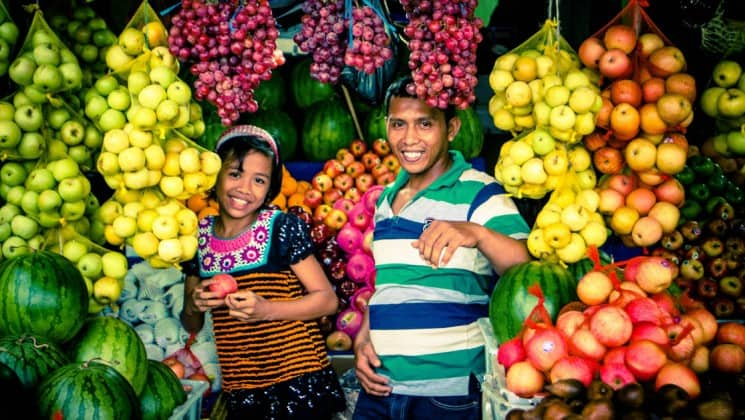 Two children stand in a fruit and vegetable stand in indonesia