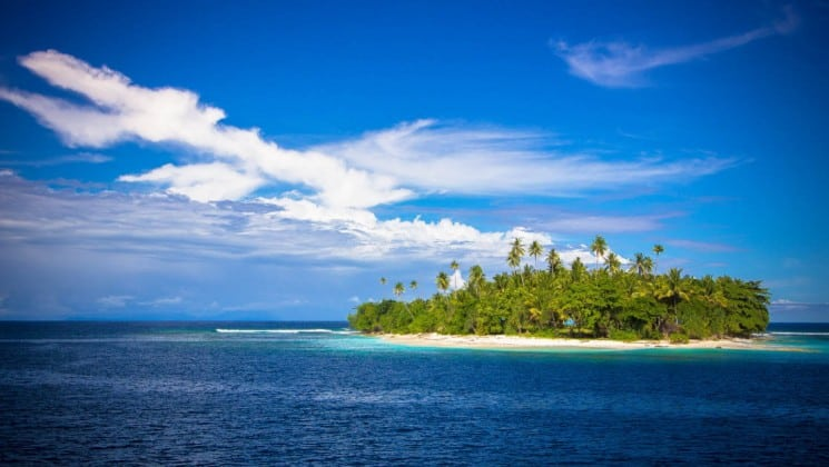 A tropical island with a jungle and a white sand beach sits on the ocean under a blue sky with clouds