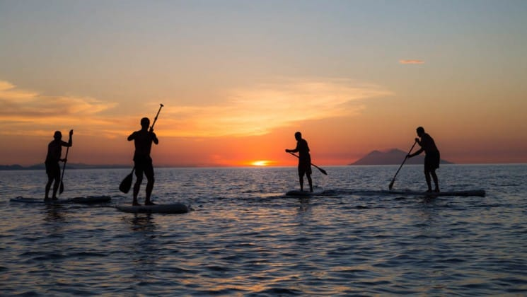 A group of people on stand up paddleboards on the ocean during a sunset in indonesia