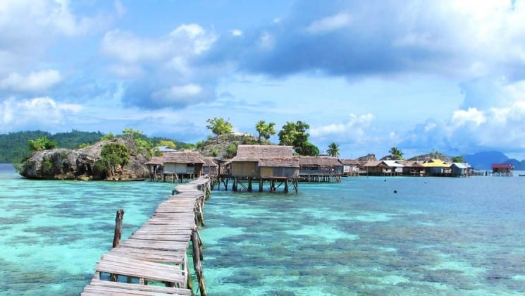 Looking toward an island in indonesia from the end of a long wooden pier over clear, tropical water