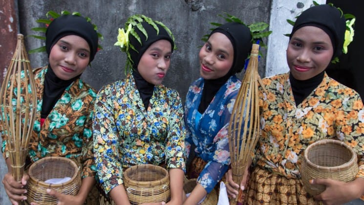 Women dressed in traditional clothing hold spice baskets in indonesia