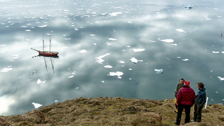 guests from the sailing spitsbergen small ship cruise hike on the tundra while the noorderlicht boat is anchored at sea below