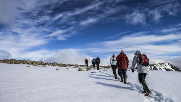 people hike on snow while on the sailing spitsbergen small ship expedition cruise