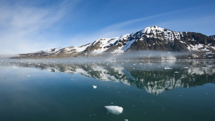 Snow-capped mountains reflected in the ocean in the arctic in spitsbergen