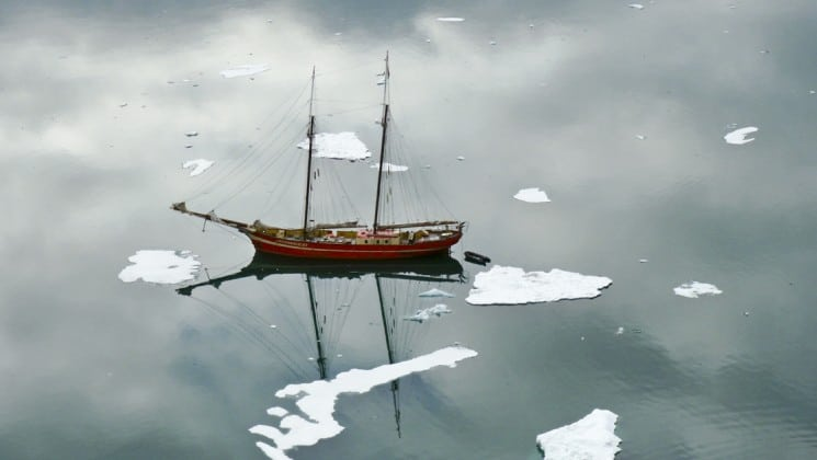 The noorderlicht small sailing ship is anchored at sea, its reflection cast in a calm ocean with ice