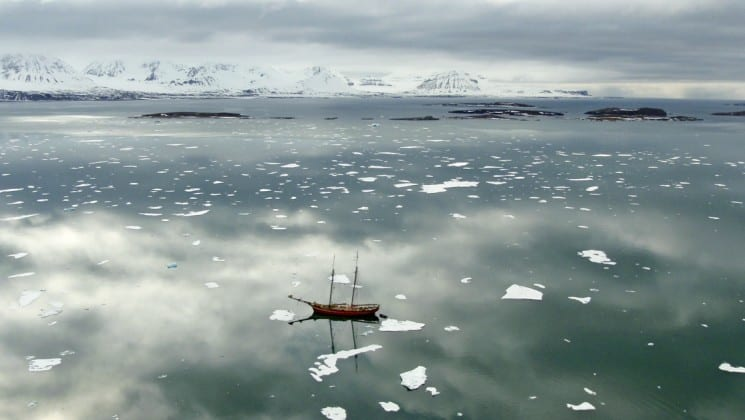 The noorderlicht small ship of sailing spitsbergen navigates an icy ocean with snow-capped mountains in the distance