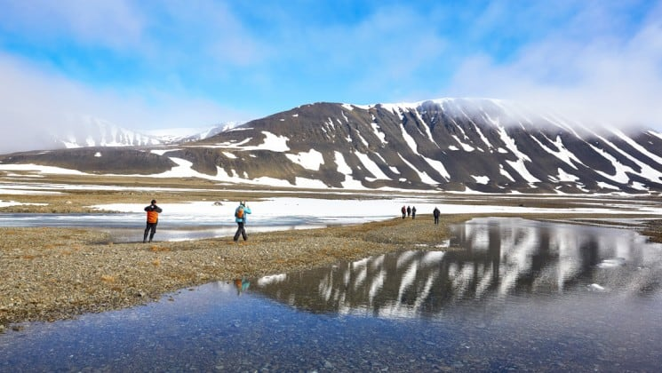 people hike on the tundra to look at the scenery and snow-capped mountains of spitsbergen