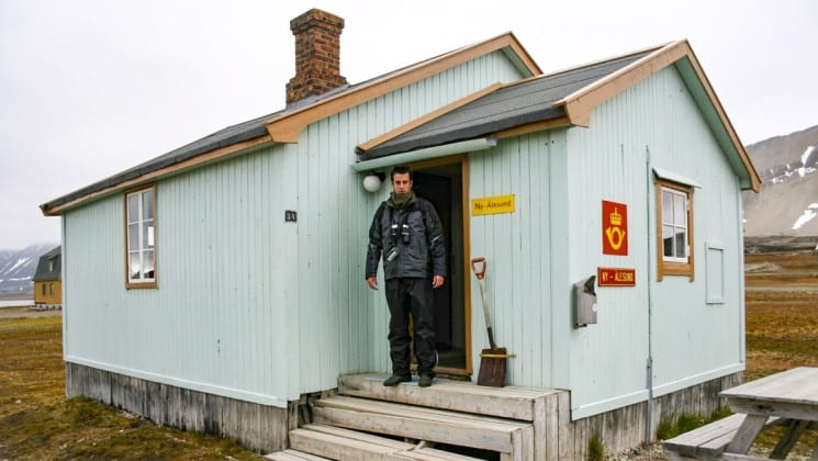 a man stands on the doorstep of the northernmost post office in spitsbergen while on a small ship cruise
