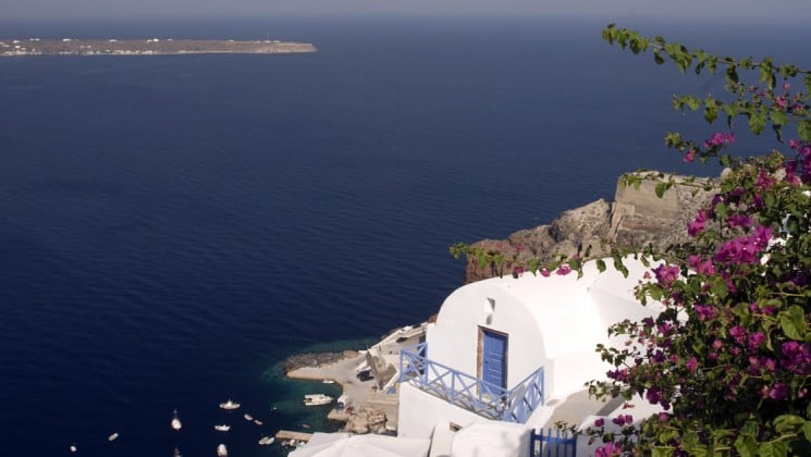 Flowers and white, domed building on the hillside overlooking the ocean in santorini