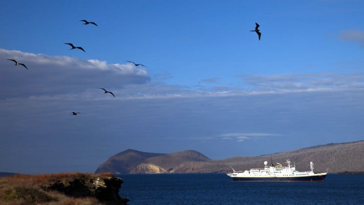 A panoramic image of the National Geographic Islander cruise ship motoring across the ocean in the Galapagos Islands, while birds fly in the sky.