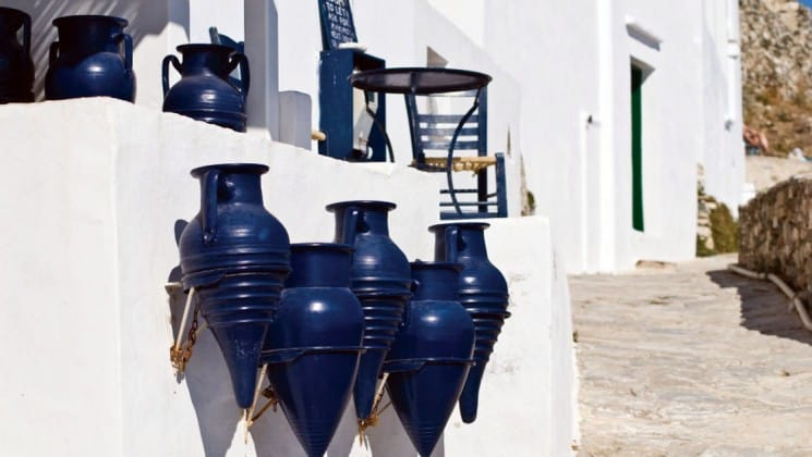 Blue ceramic pots hang on the side of a white building in sifnos greece