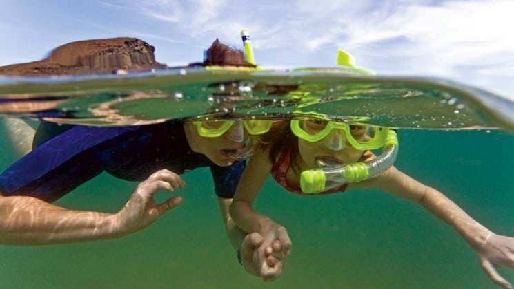 Two children with snorkels and face masks swim in the water near the National Geographic Endeavor, a luxury cruise vessel for traveling to the Galapagos Islands.
