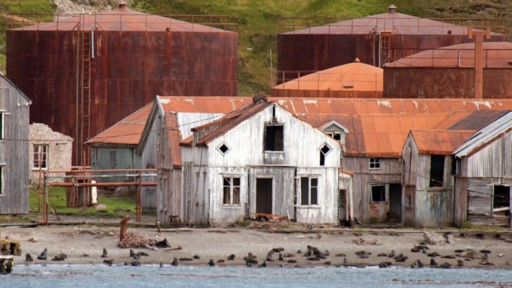 A run down white building with a rusted roof, as seen on an expedition to the falklands, south georgia and antarctica