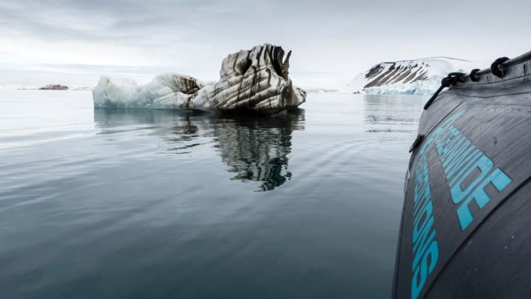 icebergs rise out of the ocean, as seen from the side of a zodiac boat on the around spitsbergen expedition cruise