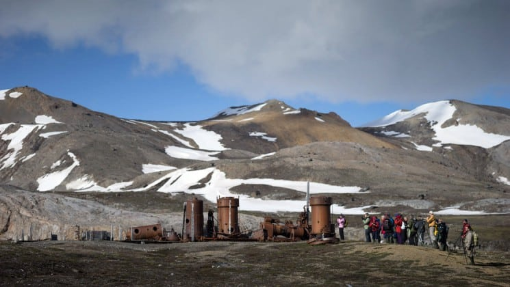passengers from the around spitsbergen expedition cruise hike on the tundra to old mining equipment in the arctic circle