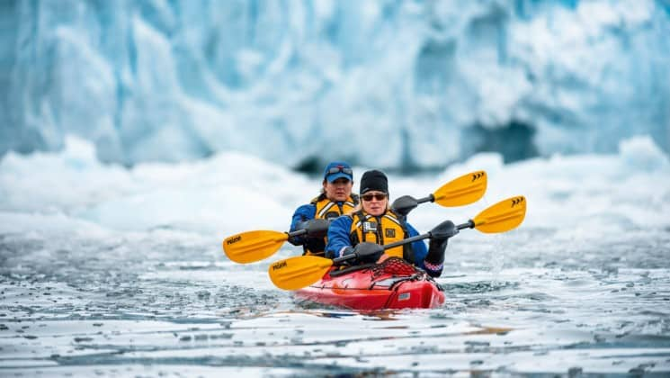 a kayak with two people paddles through frozen waters and ice caps in the arctic circle