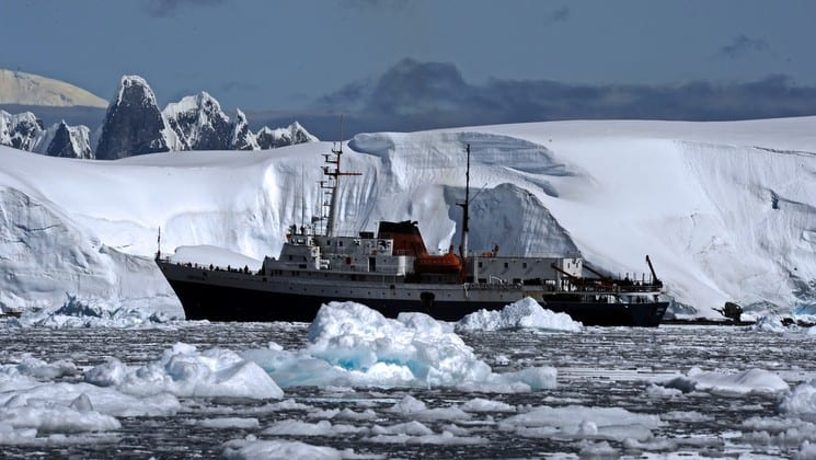 A ship cuts through the ice just in front of an iceberg in antarctica