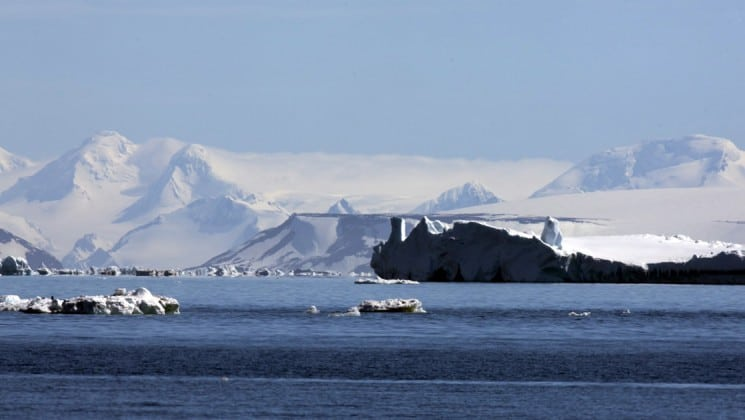The ocean in the foreground with icebergs and snow-covered mountains in the distance, as seen from the weddell sea emperor penguin voyage cruise ship.